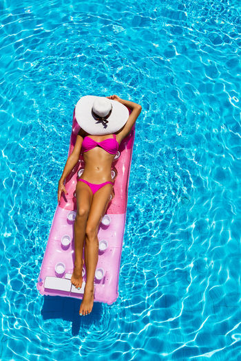 Attractive woman floating in the pool and enjoying the sun Beautiful Holiday Red Woman Attractive Bikini Blue Floating On Water High Angle View Inflatable  Leisure Activity Lifestyles Model One Person Pool Raft Relaxation Sexygirl Summer Sun Hat Sunlight Suntan Swimming Pool Vacation Vacations Water
