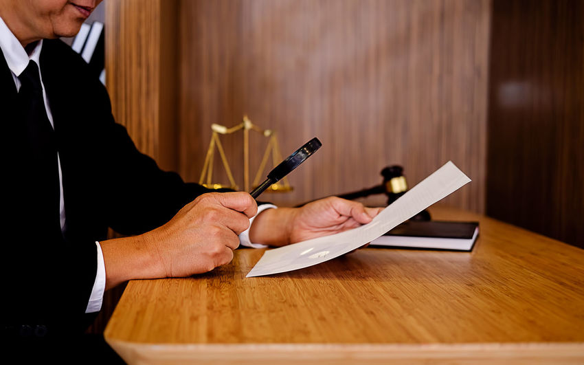 Midsection of male lawyer analyzing document while sitting in office