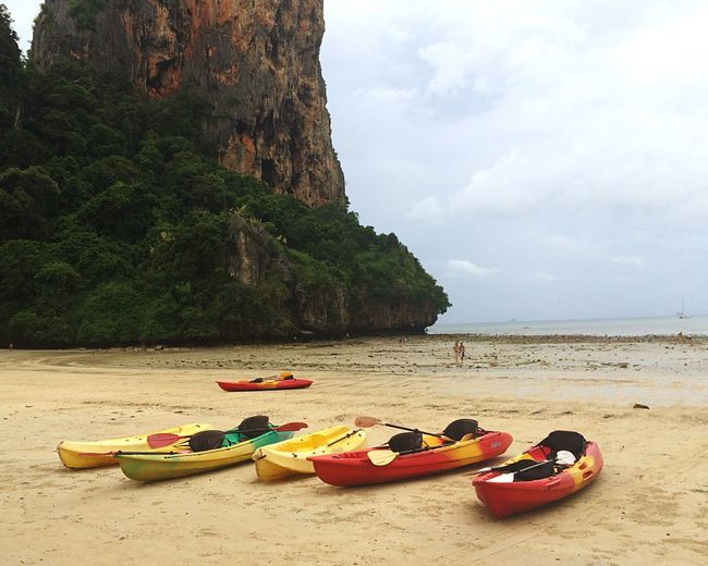 Kayaks moored at railay beach against sky