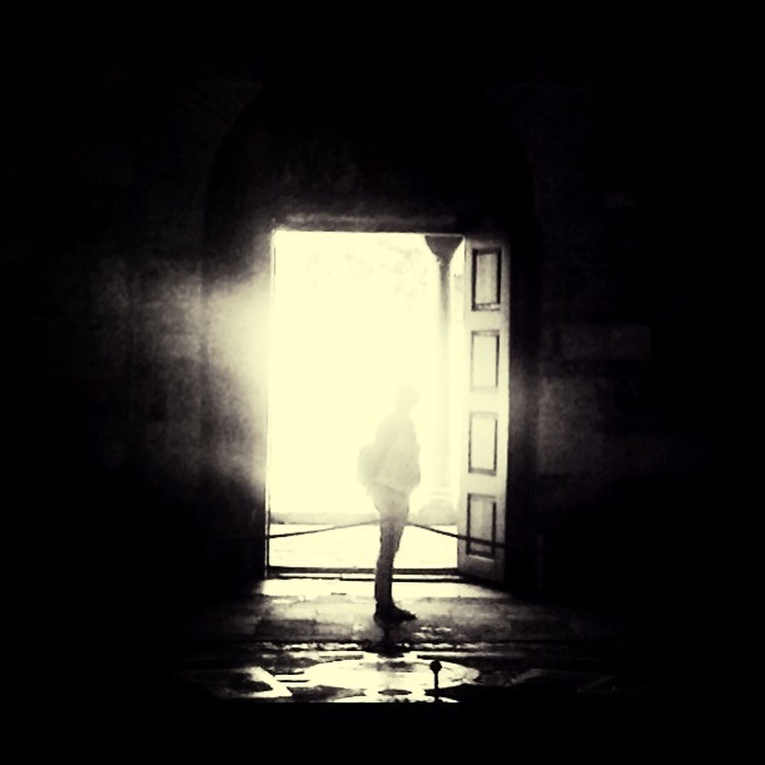 indoors, full length, standing, lifestyles, rear view, window, silhouette, sunlight, walking, person, door, architecture, arch, built structure, wall - building feature, dark, leisure activity, day