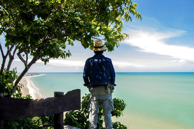 Rear view of mature man standing against sea and sky