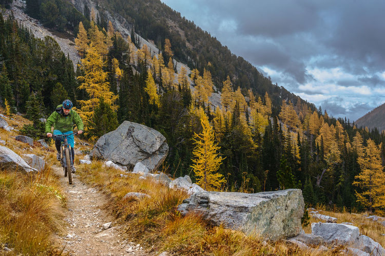 Hiker riding mountain bike on trail against cloudy sky during autumn