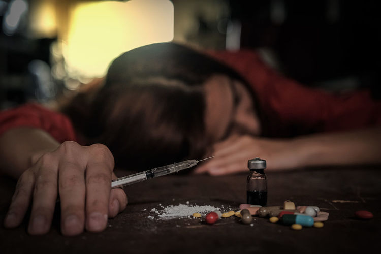 Woman holding syringe by pills and bottle on table