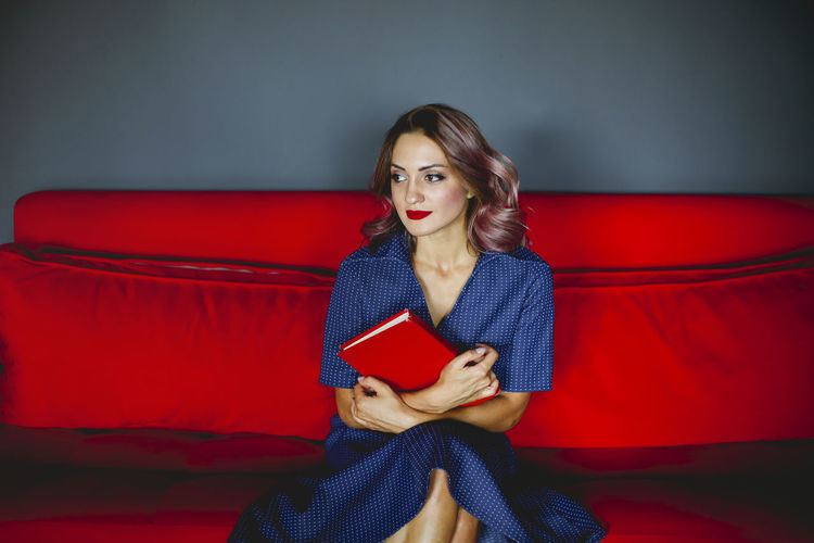Beautiful young woman holding book sitting on sofa