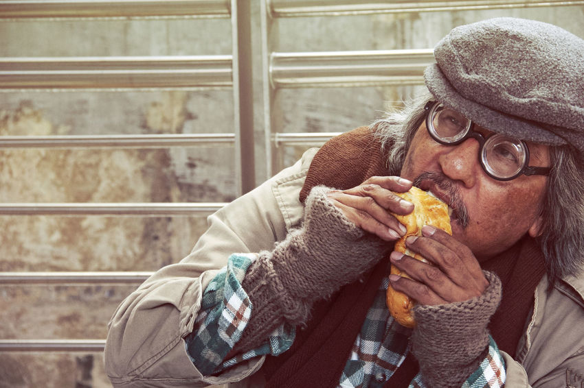 Homeless man on street and eating old bread. Adult Close-up Clothing Day Eating Eyeglasses  Food Food And Drink Freshness Front View Glasses Hat Holding Leisure Activity Lifestyles Mature Men One Person Portrait Real People Warm Clothing Winter
