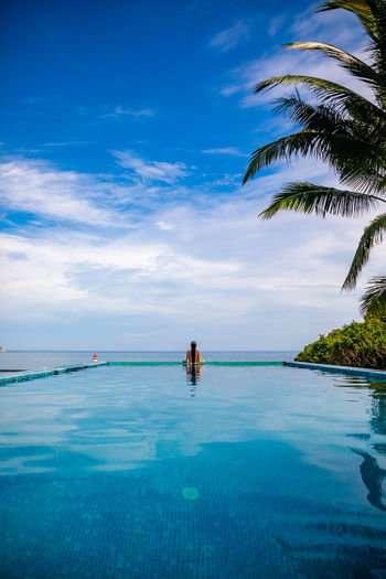 Rear view of woman in infinity pool against blue sky