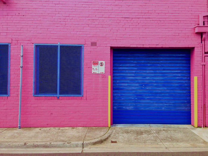 View of a a pink building with blue rolling door