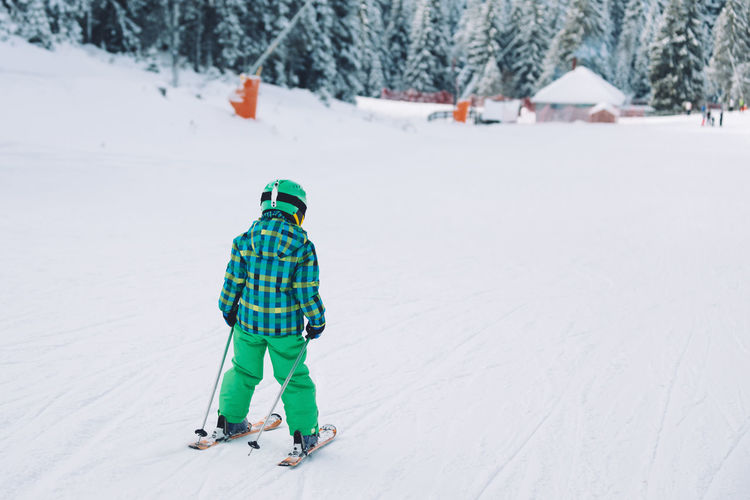 Rear view of boy skiing on snow covered land