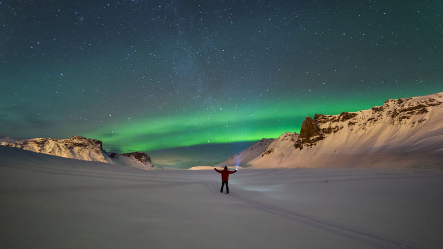 Person on mountain against sky at night