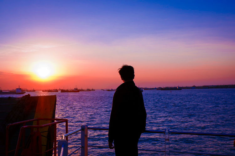 Silhouette Man Looking At Sea While Standing By Railing Against Sky During Sunset