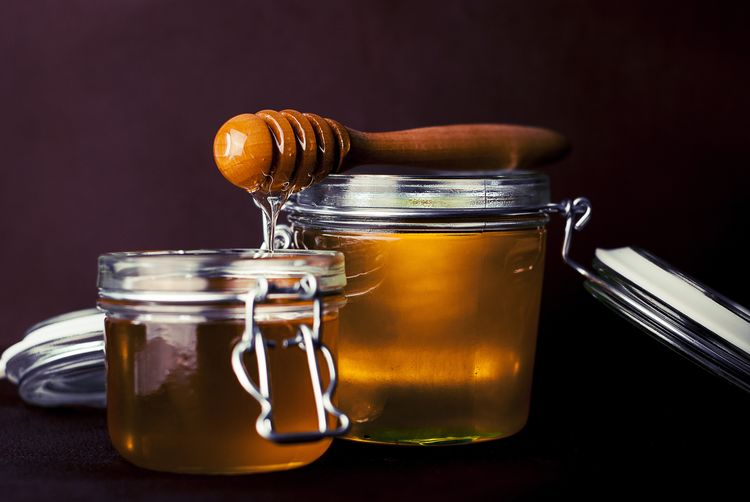Close-up of drink in honey jar on black background
