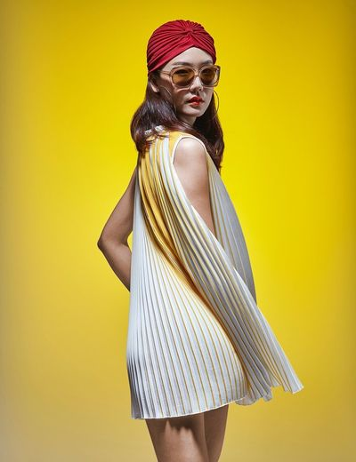 Woman wearing sunglasses standing against yellow background