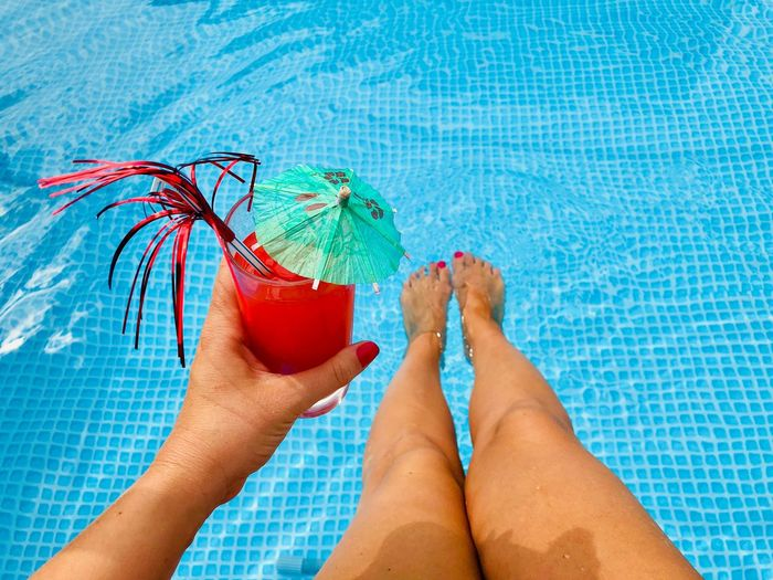 Woman's hand with red nails holding a glass of red orange juice with a small umbrella and a funny straw over the turquoise water of the pool Day Body Part Vacation Holiday Tanned Legs Feet Straw Umbrella Fresh Cocktail Blood Orange Orange Refreshment Beverage Smoothie Juice Cold Drink Drink Glass Red Nails Hand Hold Woman Swimming Pool Pool Edge Poolside Summer