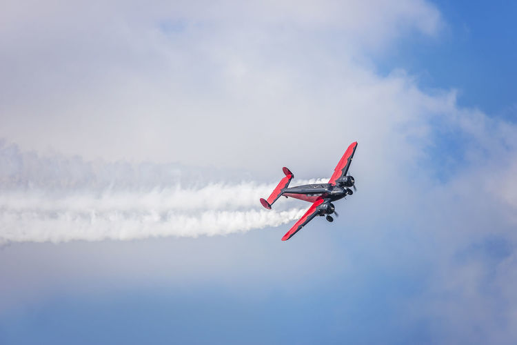 Low angle view of military airplane performing airshow against sky