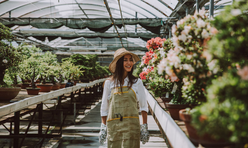 Smiling woman wearing hat standing amidst potted plants in greenhouse