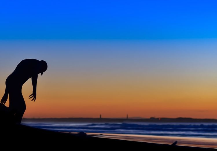 Silhouette woman at beach against sky during sunset