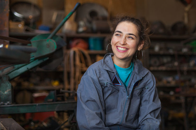 Smiling Manual Worker Looking Away While Sitting In Workshop