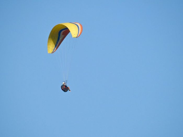 Low angle view of person paragliding against clear sky