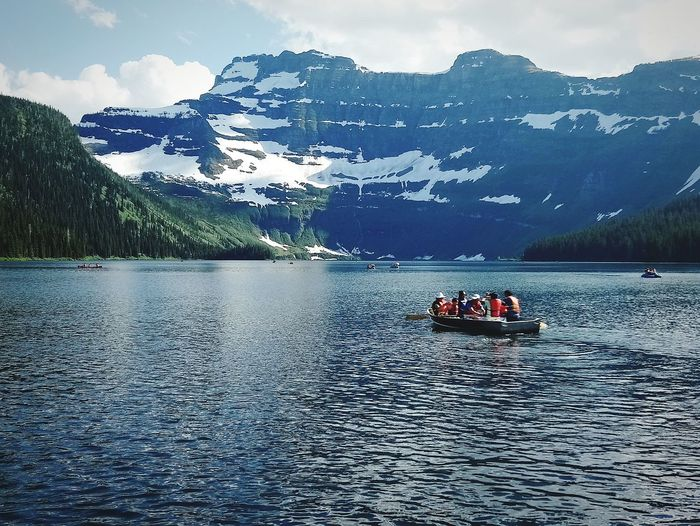 People sitting in boat on lake against mountains
