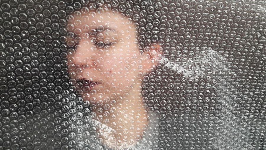 Close-Up Of Young Woman With Bubble Wrap