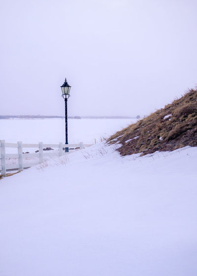 Light pole in the snow Snow Cold Temperature Winter Nature Street Light Day Sky Outdoors White Color Land No People Lighting Equipment Freezing Snowfall Light Lighting Equipment Grass Sea Water Cold Colors Rural Scene Beauty In Nature Tranquility Scenics - Nature