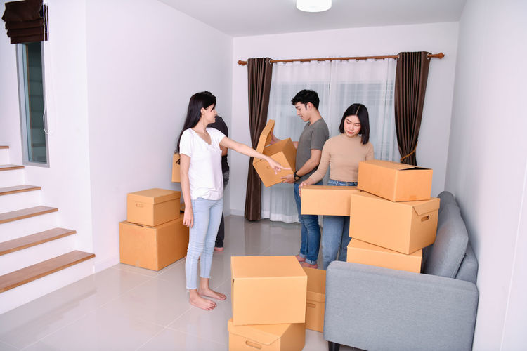 Adult Beginnings Box Box - Container Cardboard Cardboard Box Container Couple - Relationship Emotion Group Of People Home Ownership Indoors  Moving House Packing Positive Emotion Relocation Standing Teamwork Togetherness Women Young Adult Young Men Young Women