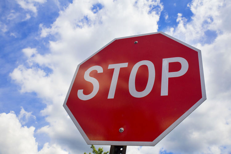 Low angle view of stop sign against cloudy sky
