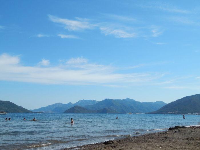 People enjoying in sea against blue sky