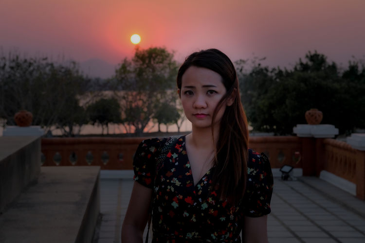 Portrait of woman standing against sky during sunset