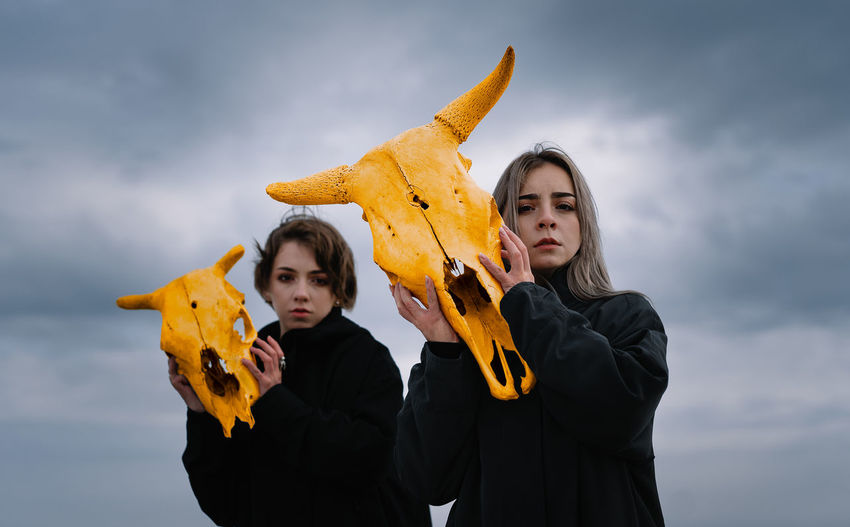 Young women holding yellow cow skull against cloudy sky