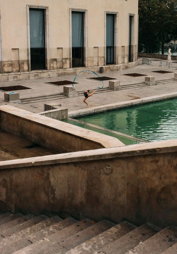 People in swimming pool by buildings in city