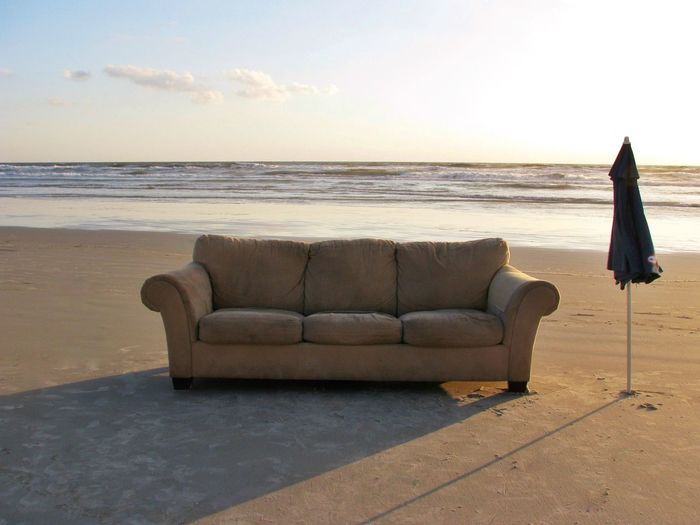 Beige couch on a beach with umbrella on sunset Journey Ocean View Beach Holiday Office Luxury Hotel Apartment Furnitures Lifestyles Living Room Resting Relaxing Lazy Day Summer Home Interior Couch Sofa Coastline Vacations Travel Destinations Tourism Sea Beach Horizon Over Water Tranquil Scene Tranquility Idyllic Sand Sunset Outdoors Scenics - Nature
