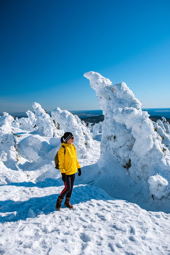 Rear view of man standing on snowcapped mountain against blue sky