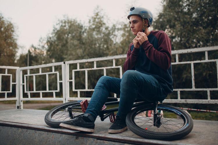 Man fastening helmet while sitting on bicycle