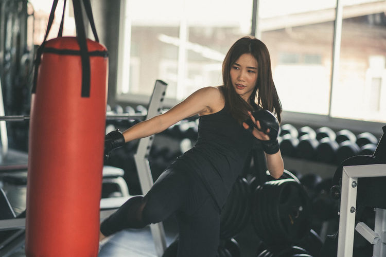 Confident Young Woman Kicking Punching Bag In Gym