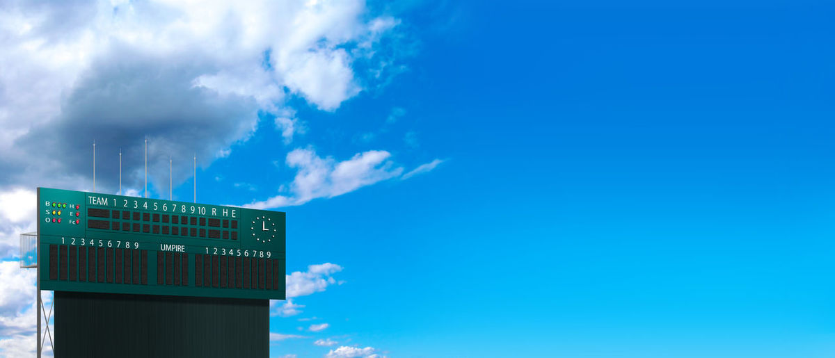 Low angle view of sign against blue sky