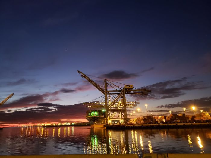 Illuminated commercial dock by river against sky at sunset