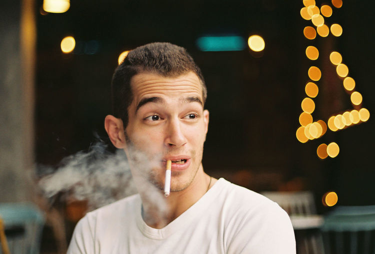 Young Man Smoking Cigarette While Sitting In Restaurant
