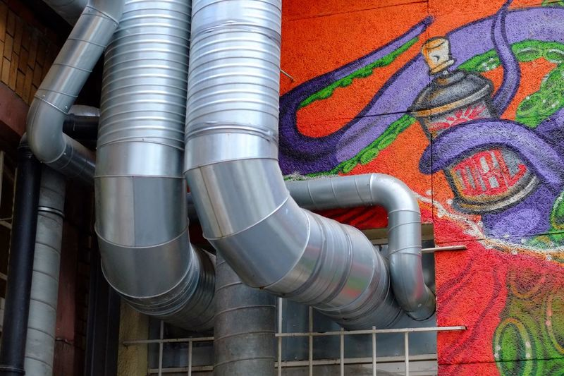 Low angle view of air ducts on graffiti wall