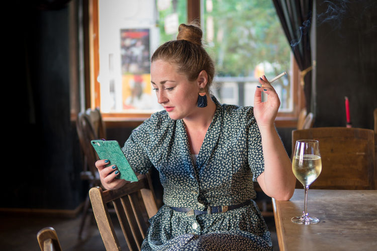 Smart Phone Technology Reading Waiting Drink Refreshment Cigarette  Bad Habit Wine Alcohol Holding Waist Up Portrait Food And Drink Beautiful Woman One Person Young Women Sitting Lifestyles Date Night - Romance Bar - Drink Establishment