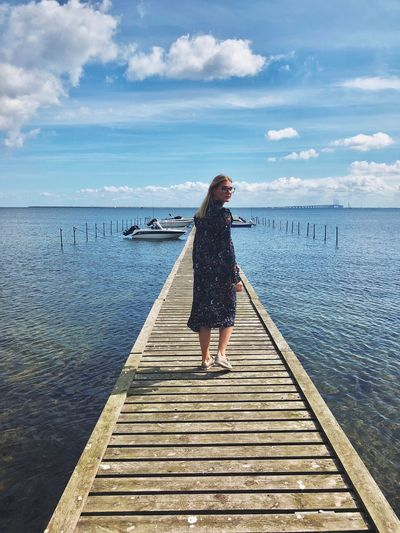 Full Length Of Woman Walking On Pier Over Lake Against Sky