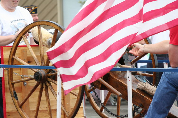 Men by cannon and american flag on street during fourth of july parade