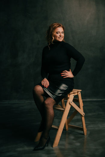 Portrait of woman sitting on chair against wall