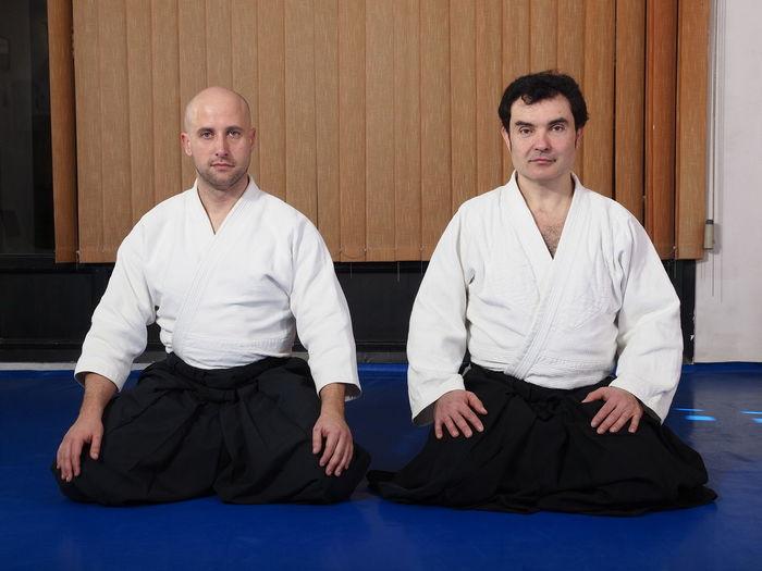 Portrait of men wearing hakama while kneeling on tatami mat