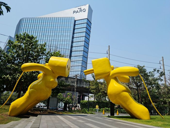 Low angle view of yellow sculpture against building