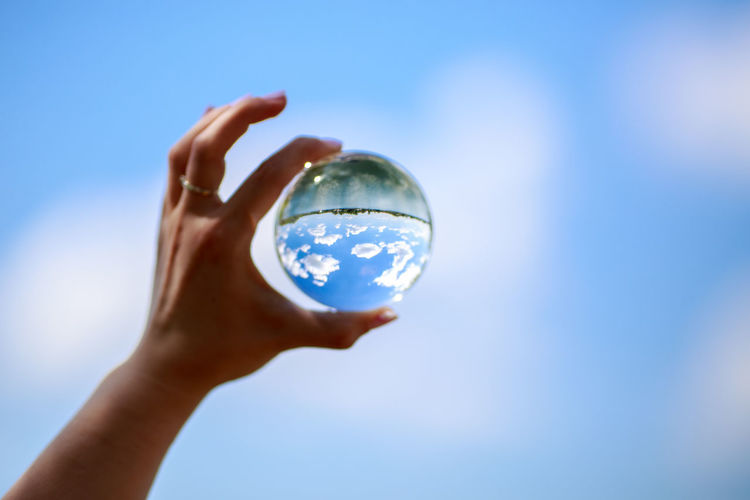 Cropped hand of woman holding crystal ball with reflection of sky