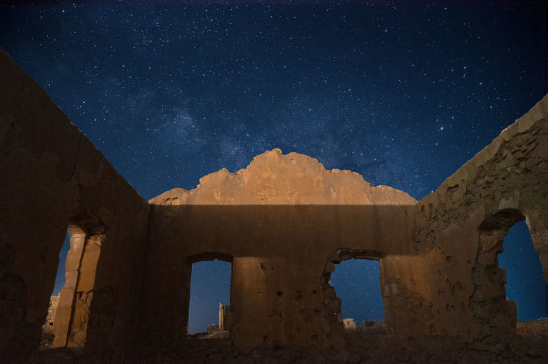 Low angle view of damaged building against sky at night