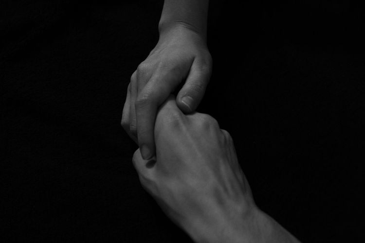 Cropped image of people holding hands against black background