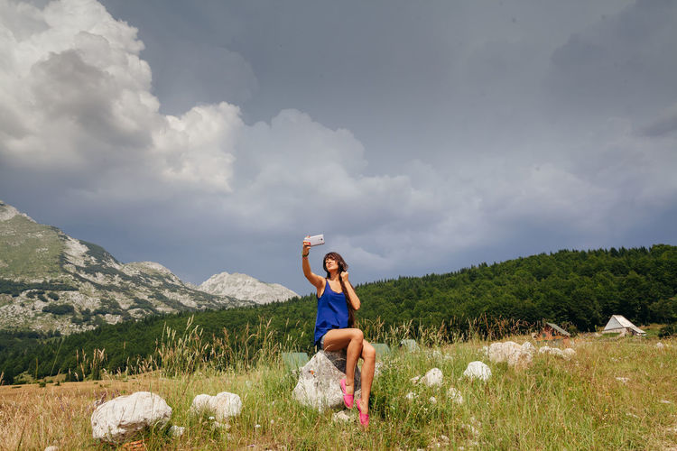 woman travel with smartphone in mountains. Authentic moments. Authentic Moments EyeEm Best Shots Long Legs Relaxing Sky And Clouds Travel Traveling Authentic Beauty In Nature Female Harmony With Nature Lifestyles Long Hair Montenegro Mountain Nature Outdoors Real People Selfie Sexygirl Sitting Sky Smartphonephotography Summer Young Adult