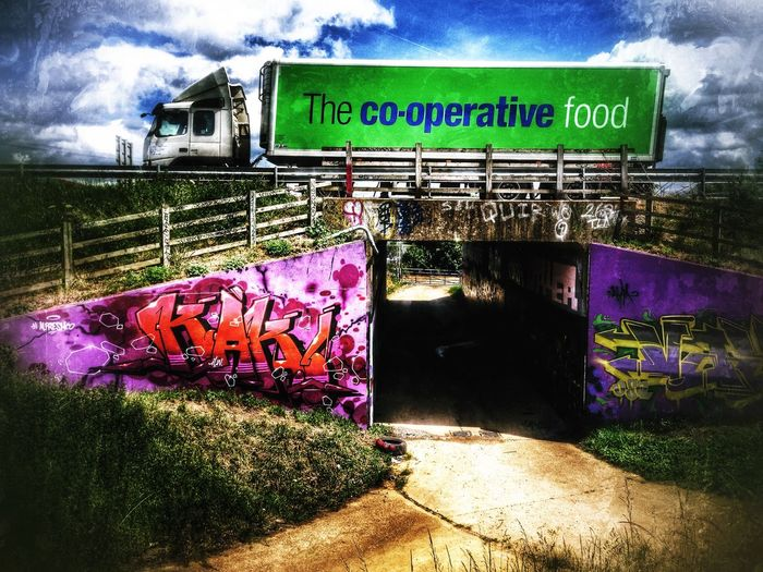 Co-op food lorry passing over subway decorated with graffiti. Eaton Scroop, Cambridgeshire, England. A1 Road British Co-Operative Coop Food Lorry English Graffiti Street Art Subway Uk Underpass Wall Painting